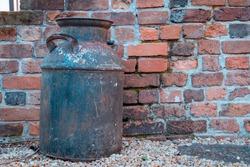 Antique milk pail against a red brick background