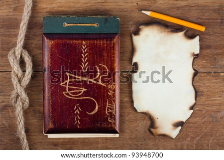 Antique notebook (1943) and burnt paper on wood with rope background