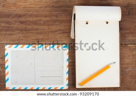 Antique Notebook (1940th), envelope, postcard and pencil on wooden background