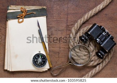 Antique notepad, compass, magnifying glass, ink pen, binoculars, rope on the old wooden background
