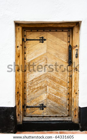 Antique oak door with black step and white wall.