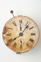 Antique object: Old withered clock of sepia colour. Roman numbers and clock face are damaged by time. Isolated object on white background.