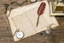 Antique office supplies and accessories on wooden table. Vintage used paper, feather pen. Nostalgic sentimental background