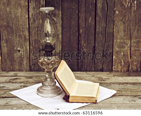 Antique oil lamp and an old book on an antique cloth on a grunge wood background.