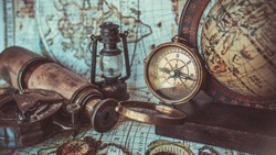 Antique old pirate rare items collections; bronze manually rotation compass, oil lamp, binocular telescope, globe model rotation on a wooden base and compass with cover lid on ancient world map.