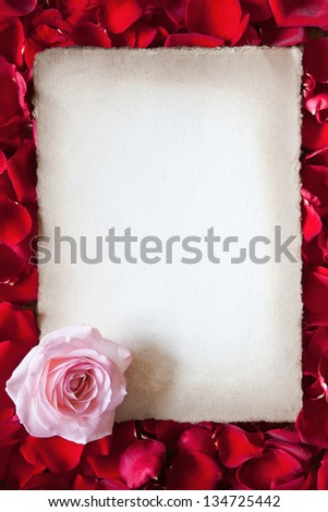 antique paper with a pink rose framed from red rose petals