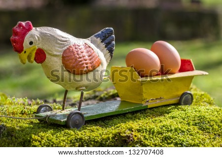 Antique papier mache rooster on a cart with eggs
