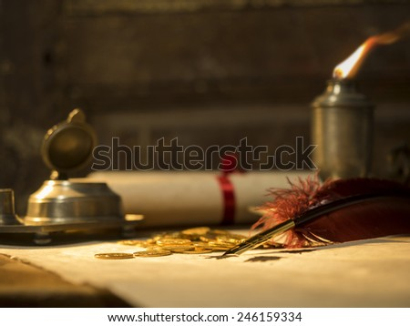 Antique parchment paper sheets lit by candlelight on a vintage colonial wood desk with ink writing feather quill, old candle light in candle-holder and gold coins