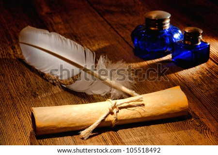 Antique parchment paper sheets roll tied by a string with and old ink writing feather quill and vintage colonial blue glass inkwells on a distressed ancient wood desk