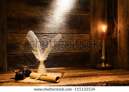 Antique parchment paper sheets roll with old writing feather quills in vintage ink well and ancient colonial blue glass inkwells on distressed ancient wood desk by candlelight in ancient historic home