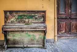 antique pianos in the street amid walls and beautiful doors