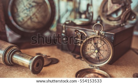 Antique pirate adventure collection including a compass, telescope, treasure wood box and globe models. (vintage style)  - Shutterstock ID 554153533