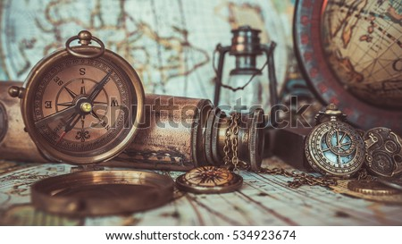 Antique pirate rare items collections including with a bronze pocket compass with cover lid, old binoculars, compass necklace, world globe base on ancient world map background.  (vintage style) - Shutterstock ID 534923674