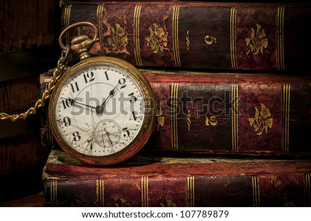 Antique pocket clock over ancient books in Low-key, copy space. Concept of time,the past or deadline.