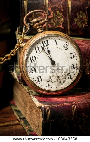 Antique pocket clock showing a few minutes to midnight over ancient books in Low-key. Concept of time,the past or deadline.