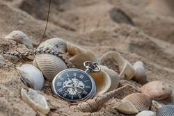 Antique pocket watch and shells in sand on the beach and copy space. Time of life in nature concept. Selective focus.