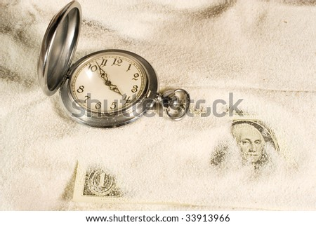 Antique pocket watch and US dollar bill covered with sand - stock photo