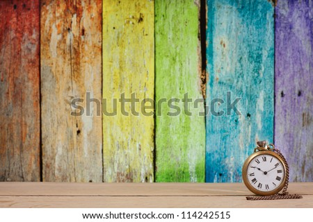 Antique pocket watch on a table in front of rainbow old wooden background. Focus on the clock