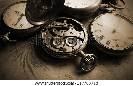 Antique pocket watch on old photos back, sepia