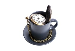 Antique pocket watch with a chain in a coffee cup isolated on white. Coffee time concept.