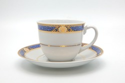 antique porcelain blue tea cup on saucer with gold edging isolated on white background