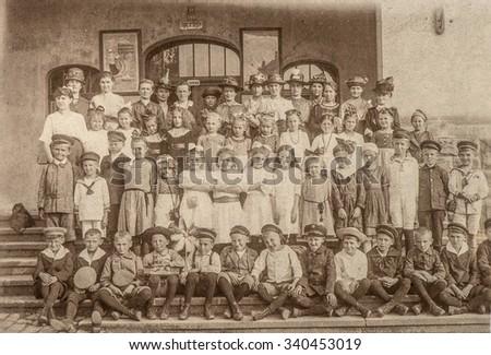 Antique portrait of school classmates. Group of children and teachers outdoors. Vintage picture with original film grain and blur