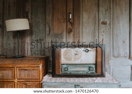 Antique radio / receiver and desk lamp on wooden chest and rattan cabinet against wooden wall / windows. #1470126470