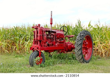 Antique red tractor in front of a corn field. Michigan, U.S.A.  12MP camera.
