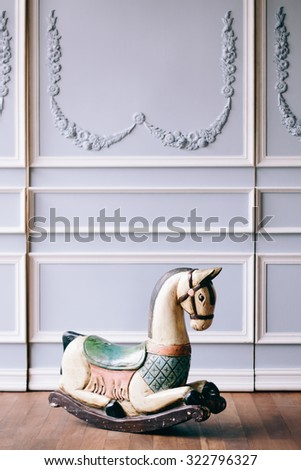 Antique reproduction wood toy rocking horse on vintage background and wooden floor - Vintage grunge empty interior, Selective Focus