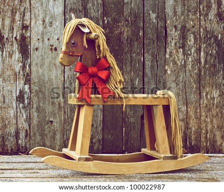 Antique rocking horse with a sparkling red Christmas bow around his ...