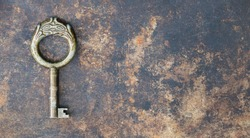 Antique rusty ornate key on grunge metal background, escape room game concept, web banner with copy space