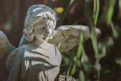 Antique sad angel statue in the garden
