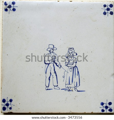 Antique seventeenth century Delft blue and white tile. Image of a Dutch woman and man. Man in costume and hat, woman in typical Dutch farmers costume