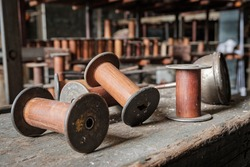 antique silk thread spools made of wood and metal sit on an old abandoned factory shelf