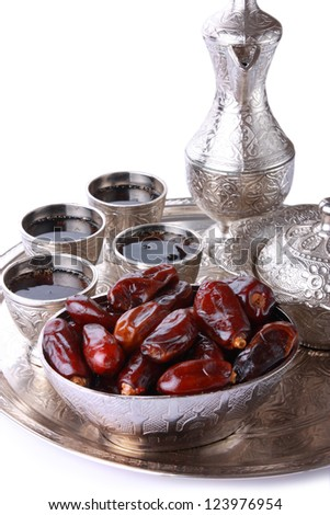 Antique silver pitcher and coffee cup set with dates in a tray isolated on a white background vertical Including clipping path