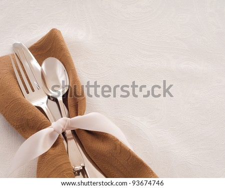 Antique Silverware Place Setting in a Brown Napkin and Tied with a Satin Ribbon against a White Background, a Table Cloth with Room for Text or Copy
