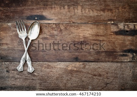 Photo of Antique silverware spoon and fork over a rustic old wooden background. Image shot from overhead.