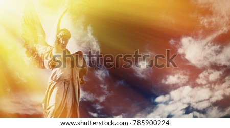 Antique sstatue of wonderful angel in the rays of the sunl on sky background (architecture, sculpture, religion, faith concept)