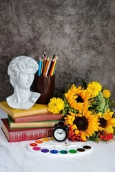 antique statue bust, flowers, alarm clock, books, watercolor paint on table. back to school concept. autumn seasonal composition. fall time. Knowledge Day