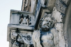 Antique stone Atlas sculpture on the wall of old building in Saint Petersburg, dramatic male statue close up