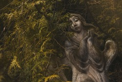 antique stone sculpture in the park of a sad angel praying