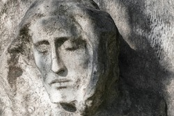 Antique stone statue of Jesus Christ, against a background of gray stone.