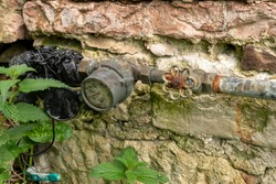 Antique stone wall texture background with water meter close up and grass