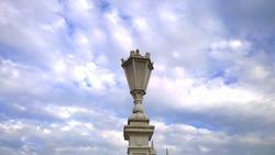 Antique street lamp against cloudy blue sky. Streetlight. Light post. Vintage architecture details. City Illumination.
