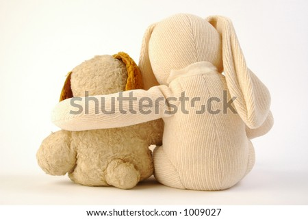 Antique stuffed dog and generic stuffed bunny on white background