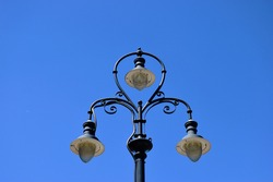 Antique style black iron street lamp post and arms with white glass covers. isolated on clear blue sky. low angle view. old classical lighting industry concept. richly decorated consol arms.