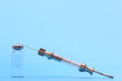 antique syringe made of metal and glass and phial on a blue background. free space for text. copyspace