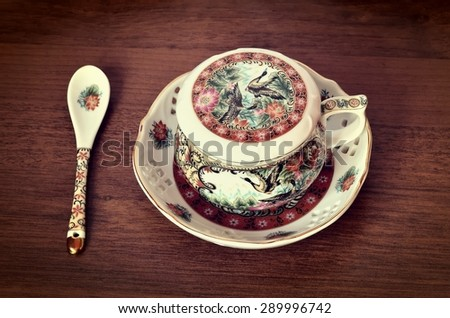 Antique tea cup. Porcelain teacup, saucer and spoon with rich ornament in classic with natural wood background.
