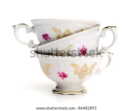 Antique tea cups stack on white background