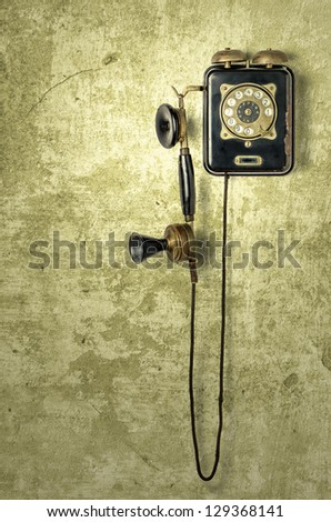 antique telephone on a grungy yellow wall